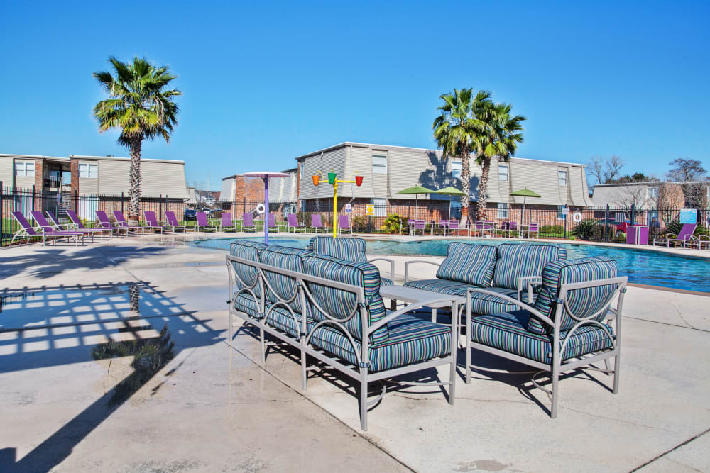 Lounge chairs near pool at Emerald Pointe Apartment Homes In Harvey