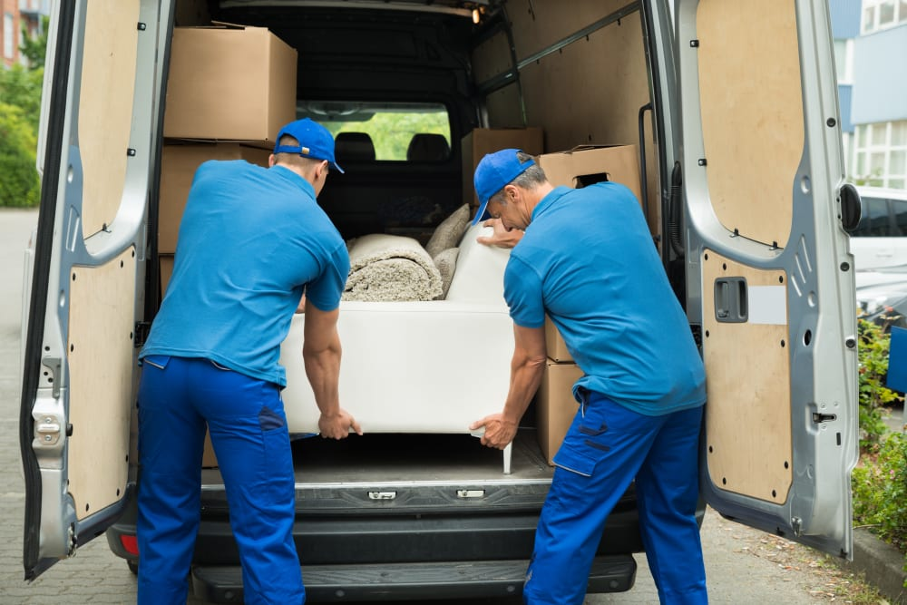 Movers removing a couch from a moving truck into storage at Storage Units in Kissimmee, Florida