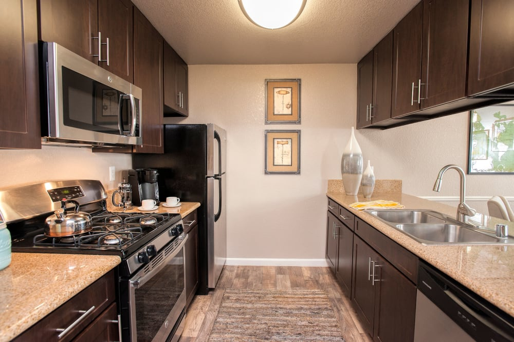 An updated kitchen with stainless steel appliances, brown cabinets and plenty of counter space at Deer Valley Apartment Homes in Roseville, California