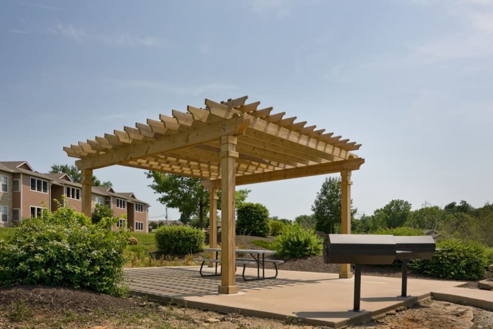Pergola over picnic tables with barbecue grill nearby at Timber Lakes Apartment Homes in Kansas City, Missouri