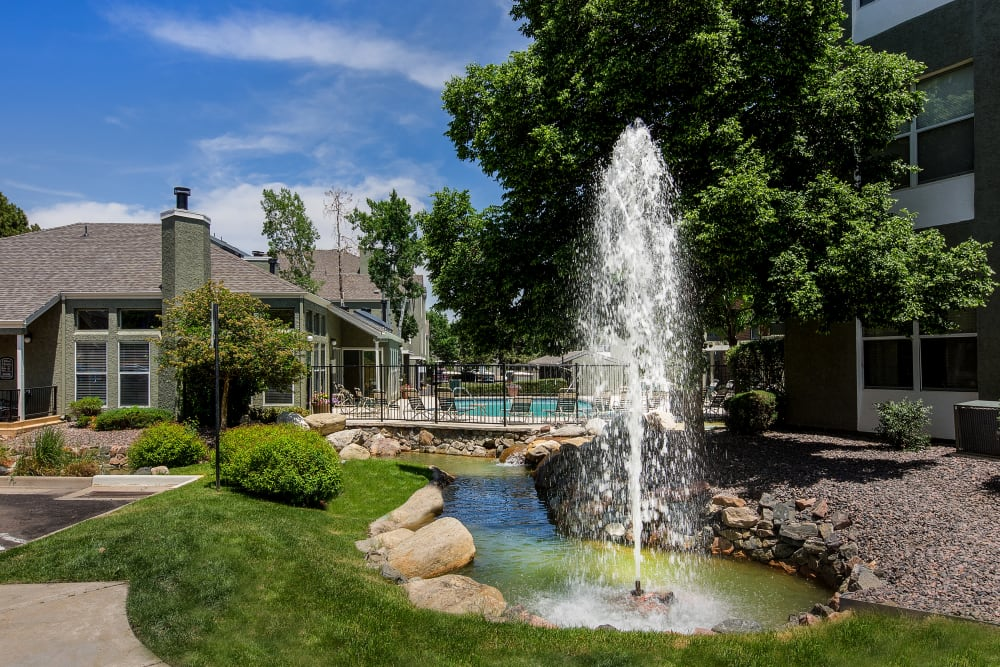 Fountain surrounded by green flora at Waterfield Court Apartment Homes in Aurora, Colorado