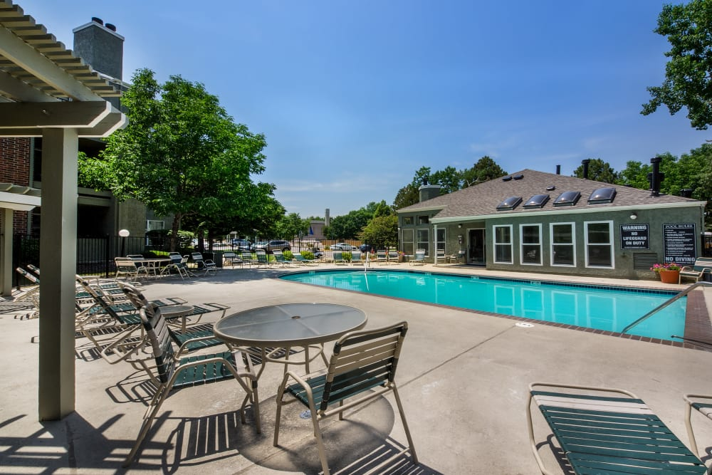 Tables and chairs near the pool at Waterfield Court Apartment Homes in Aurora, Colorado