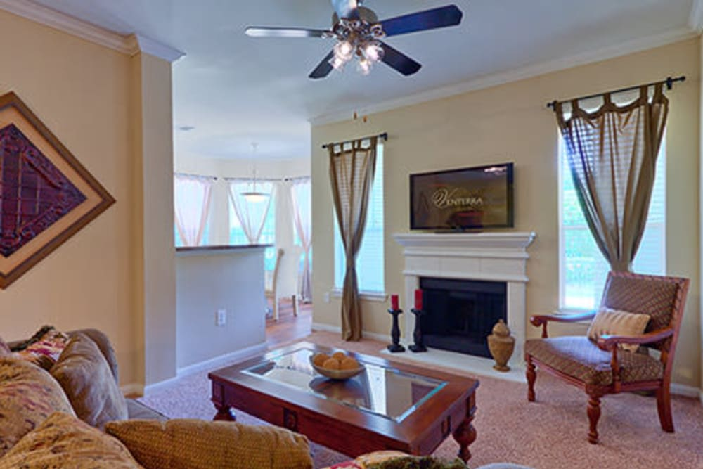 Spacious living room with a ceiling fan and fireplace at Somerset at Spring Creek in Plano, Texas