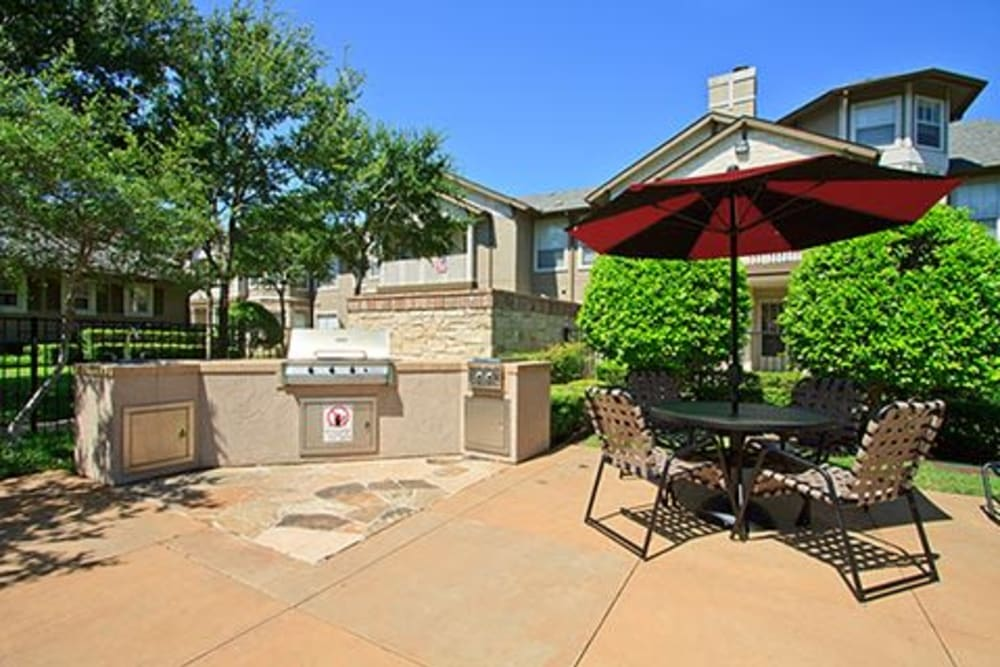 Poolside BBQ with table and chairs at Somerset at Spring Creek in Plano, Texas
