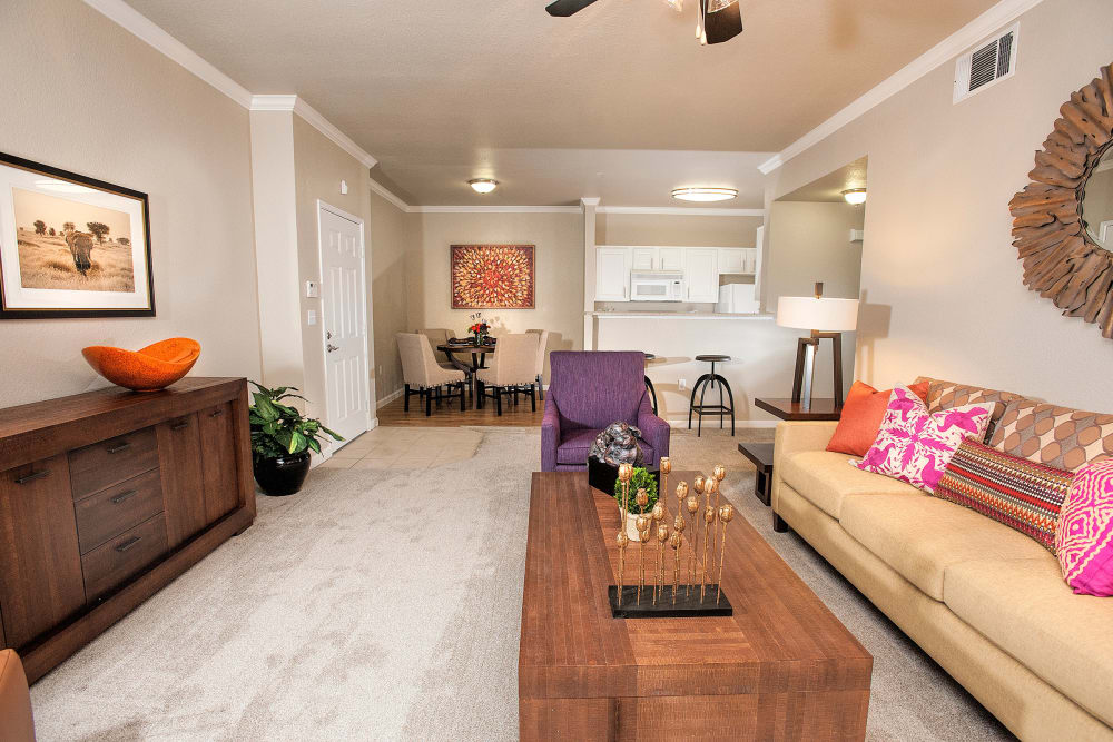 Living room with plush carpeting and a ceiling fan at River Oaks Apartment Homes in Vacaville, California