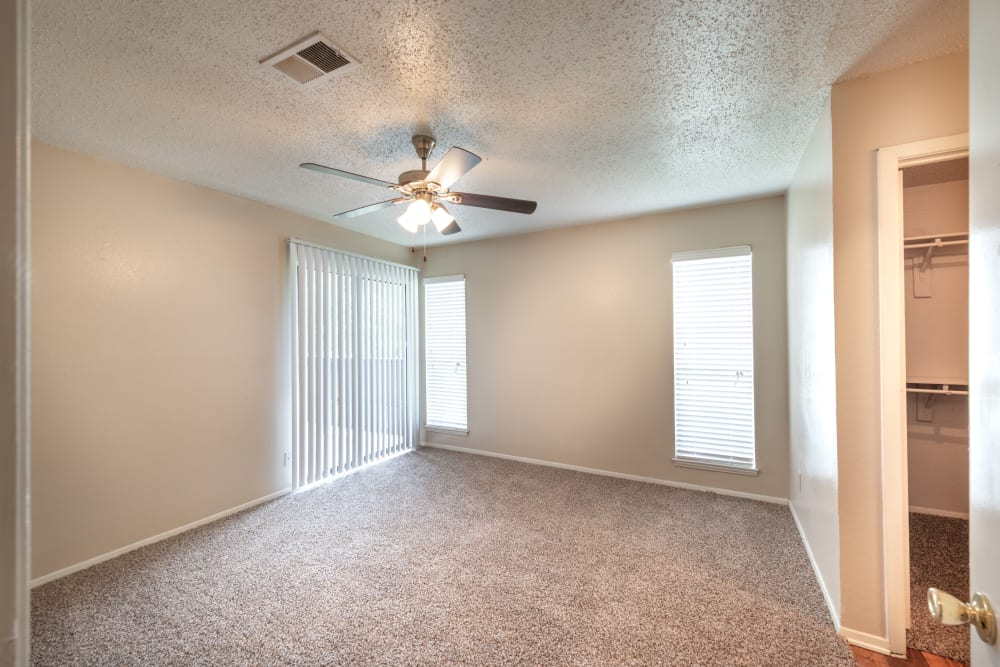 Master bedroom with plush carpeting and a ceiling fan in an apartment home at The Madison in Dallas, Texas