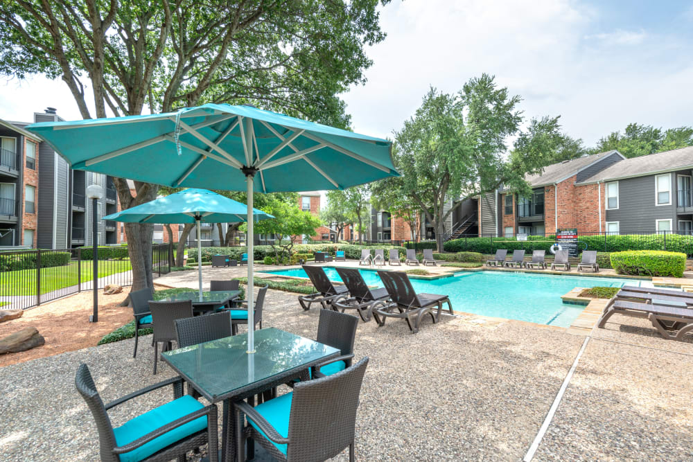 Shaded tables and chairs near the pool at The Madison in Dallas, Texas