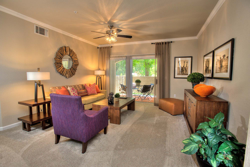 Living room with a private balcony access at River Oaks Apartment Homes in Vacaville, California