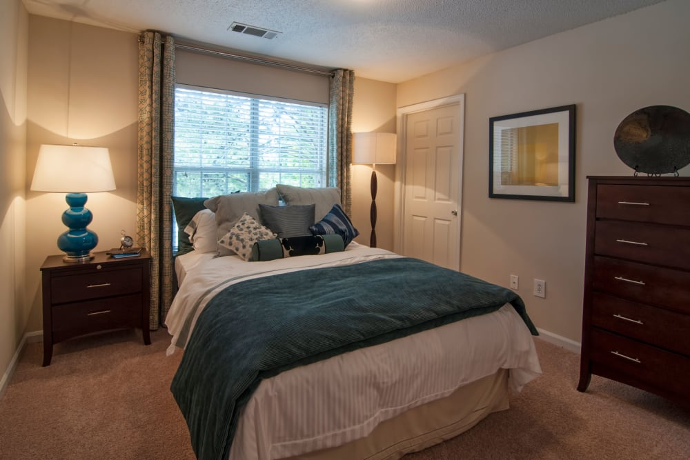 Well-furnished master bedroom with plush carpeting in a model home at Bellingham Apartment Homes in Marietta, Georgia