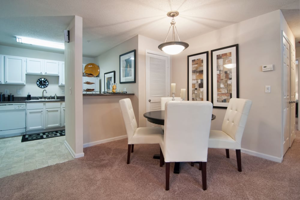 Open-concept layout with plush carpeting and custom lighting over the dining area in a model home at Bellingham Apartment Homes in Marietta, Georgia