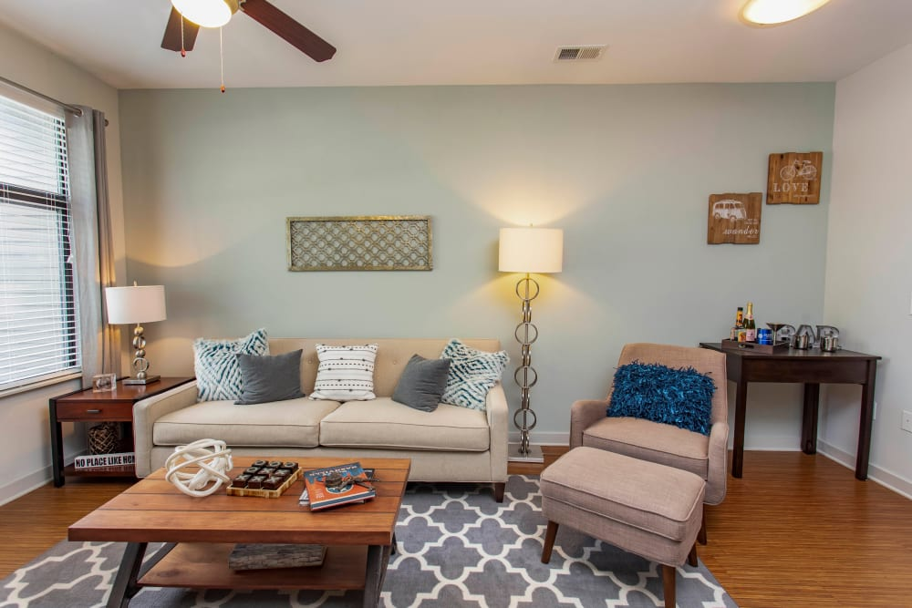 Comfortably furnished living area with an accent wall and hardwood flooring in a model home at Olympus Midtown in Nashville, Tennessee