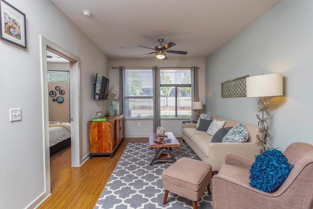 Comfortably furnished living space with a ceiling fan in a model home at Olympus Midtown in Nashville, Tennessee