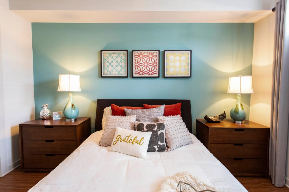 Well-furnished model home's master bedroom with an accent wall at Olympus Midtown in Nashville, Tennessee
