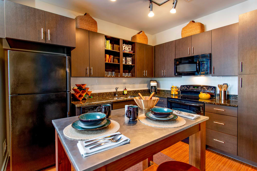 Gourmet kitchen with an island and rich wood cabinetry in a model home at Olympus Midtown in Nashville, Tennessee