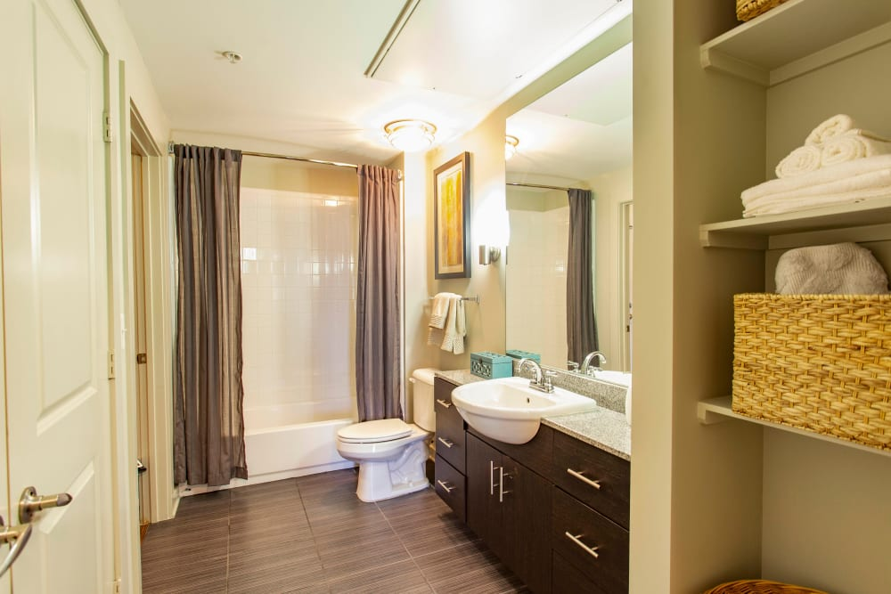 Spacious master bathroom with extra storage in a model apartment at Olympus Midtown in Nashville, Tennessee