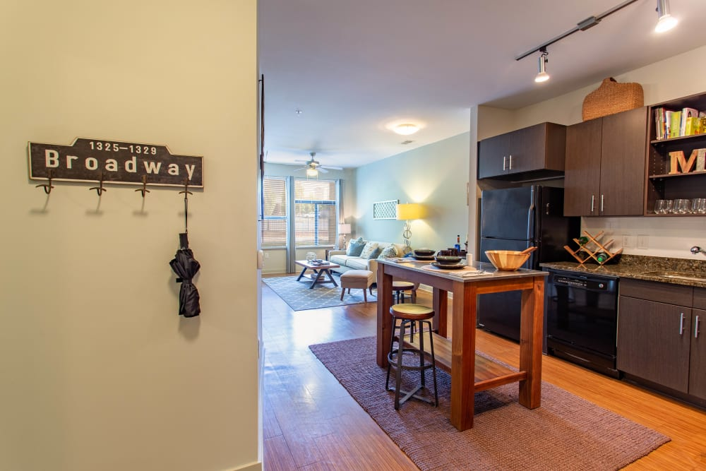 Open-concept gourmet kitchen with black appliances in a model apartment at Olympus Midtown in Nashville, Tennessee