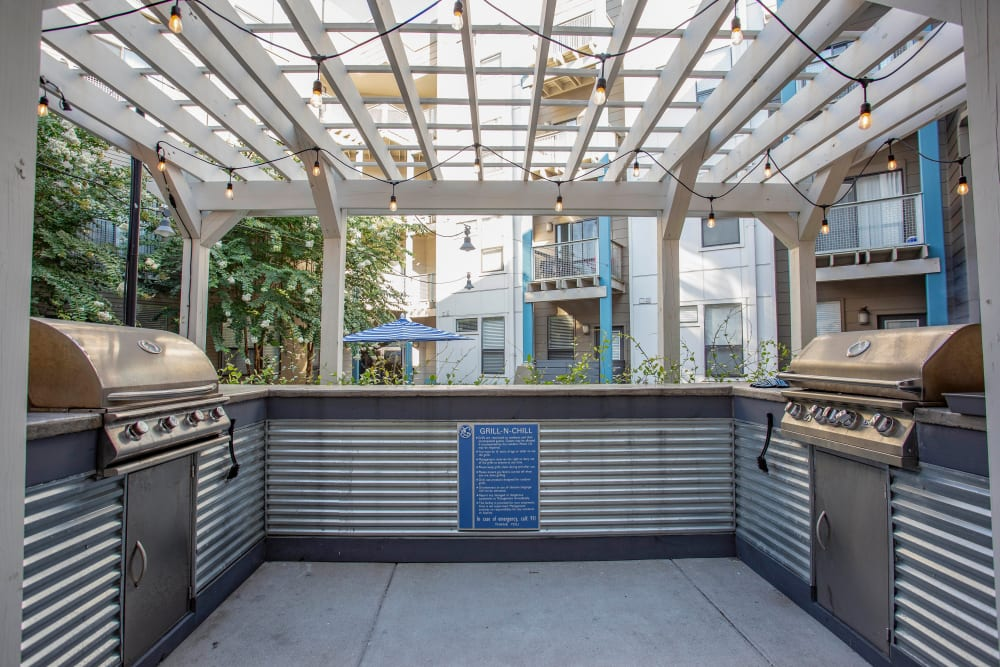 Gas grills and a pergola overhead at the barbecue area at Olympus Midtown in Nashville, Tennessee