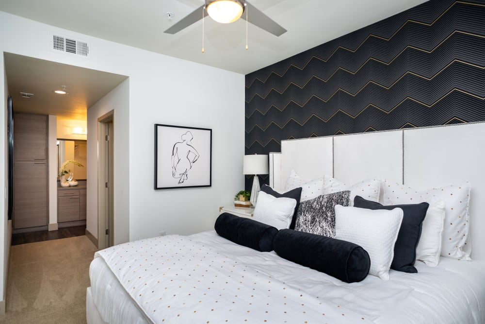Ceiling fan and modern furnishings in a model apartment's master bedroom at Fusion Apartments in Irvine, California