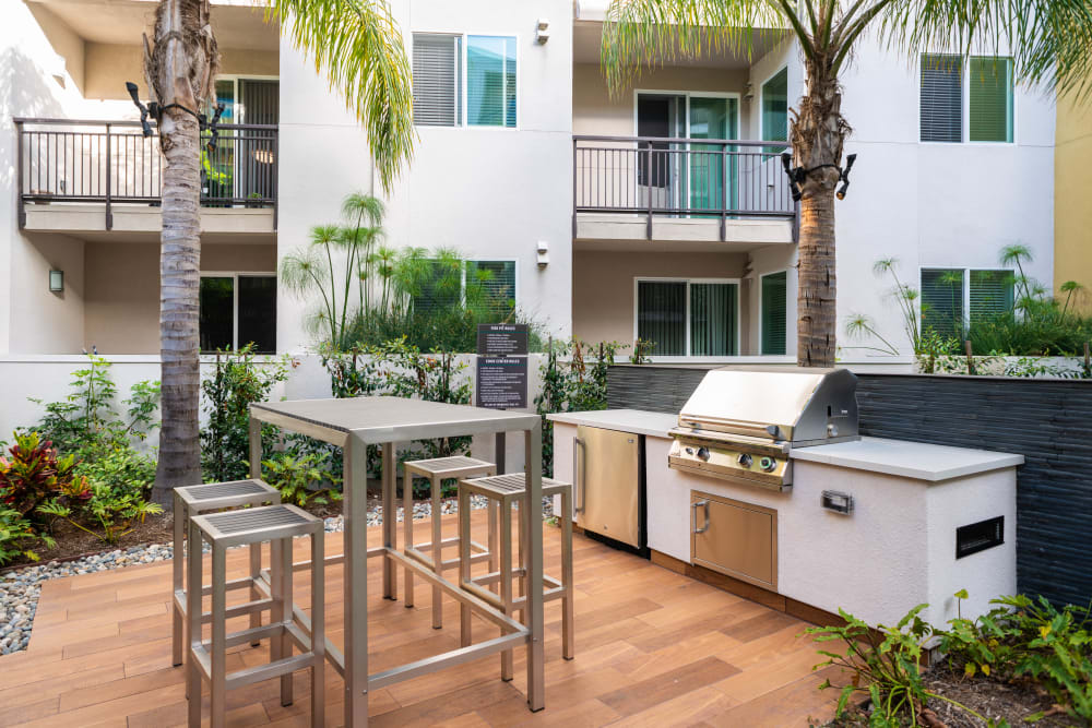 Barbecue area with gas grills at Fusion Apartments in Irvine, California