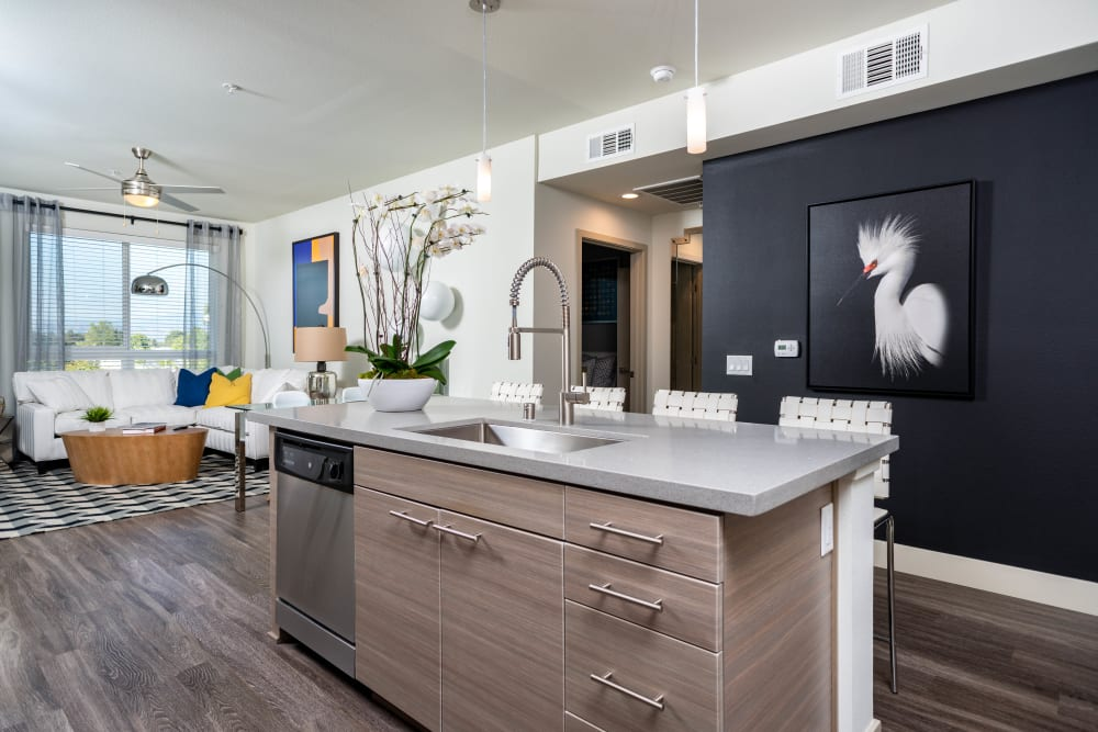Open-concept model home's kitchen with an island and granite countertops at Fusion Apartments in Irvine, California