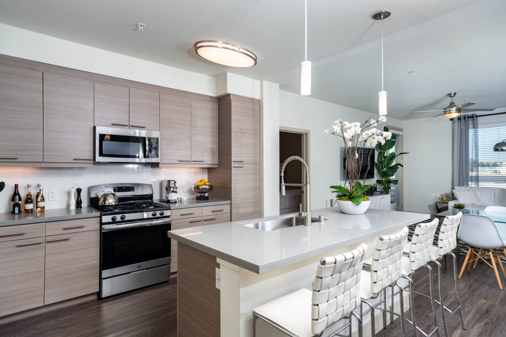 Modern gourmet kitchen with custom wood cabinetry in a model home at Fusion Apartments in Irvine, California