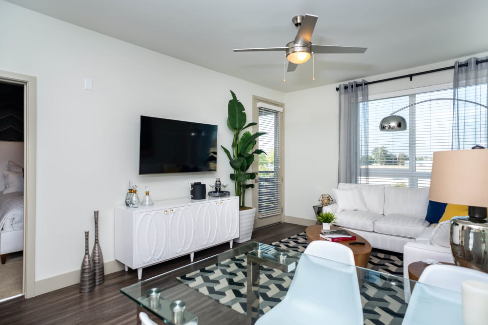 Large bay windows and a ceiling fan in the living area of a model apartment at Fusion Apartments in Irvine, California