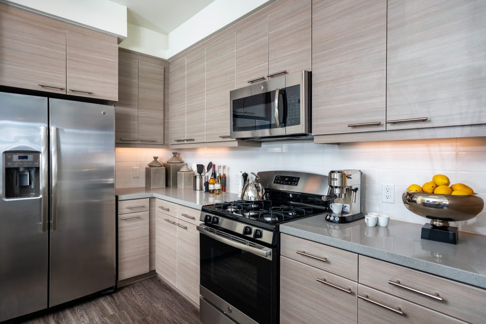 Quartz countertops and custom wood cabinetry in a model home's kitchen at Fusion Apartments in Irvine, California