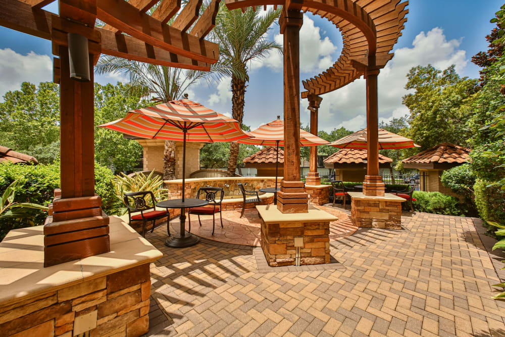 Tables with umbrellas by pool at Broadstone Toscano in Houston, Texas