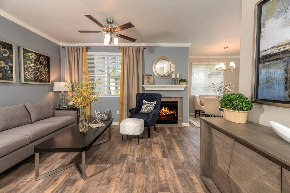 A living room with a ceiling fan and wood-style flooring at The Artisan Apartment Homes in Sacramento, California