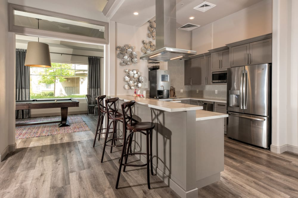 Clubhouse kitchen with bar seating at The Artisan Apartment Homes in Sacramento, California