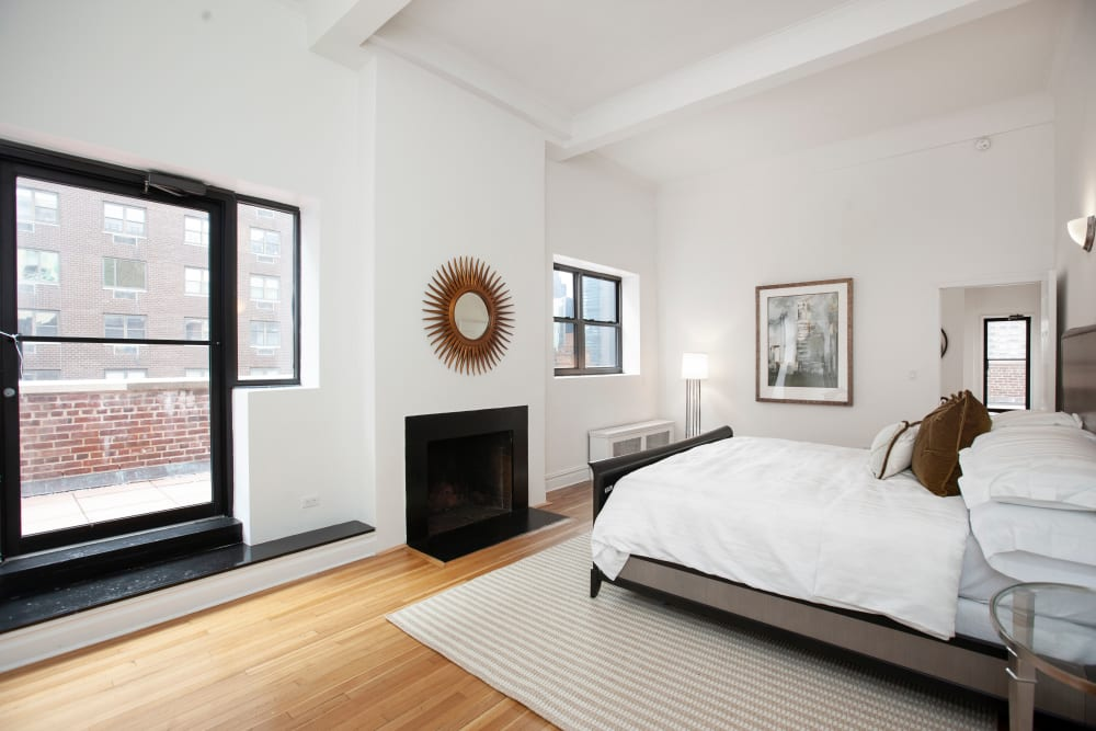 Large main bedroom with a fireplace and balcony at The Sutton Collection in New York, New York