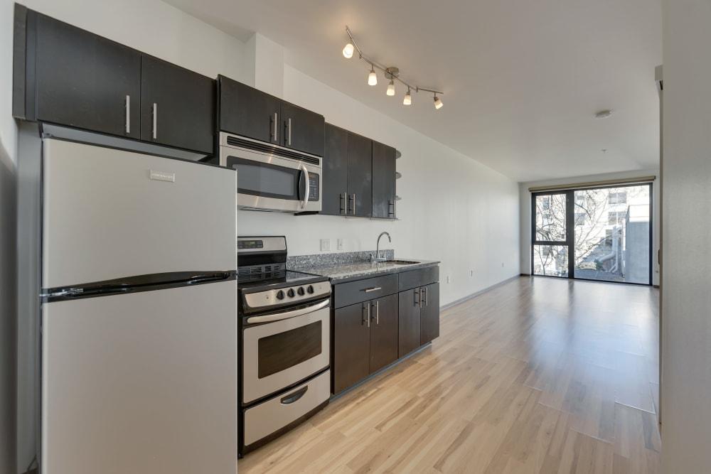 Modern, sleek kitchen with wood-style flooring at Milano in Portland, Oregon