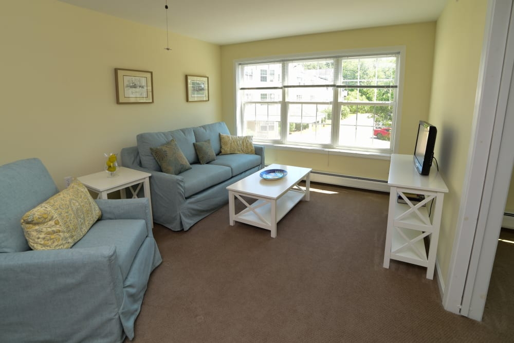 A living room with large windows at Harbor Village Senior Communities in South Burlington, Vermont