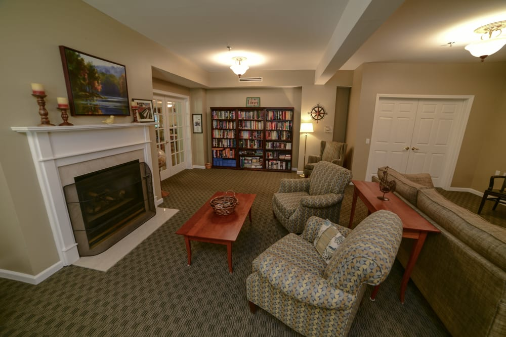 A community area with a fireplace at Harbor Village Senior Communities in South Burlington, Vermont