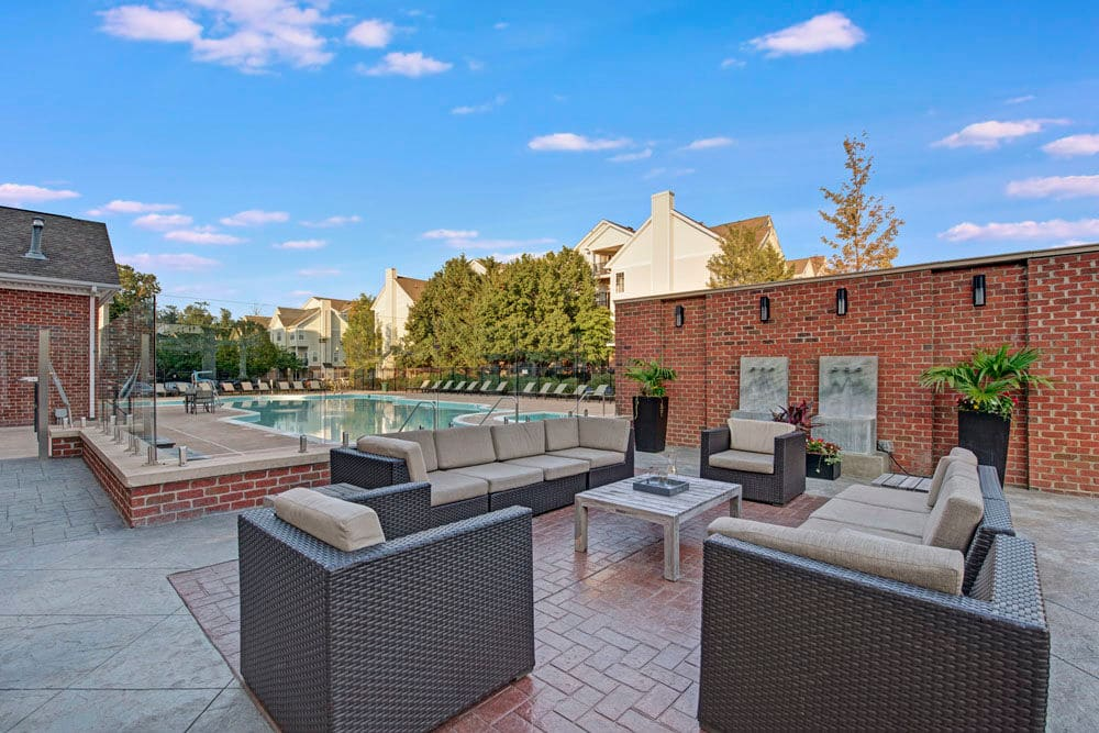 Outdoor community seating area by swimming pool at Dulles Greene in Herndon, Virginia