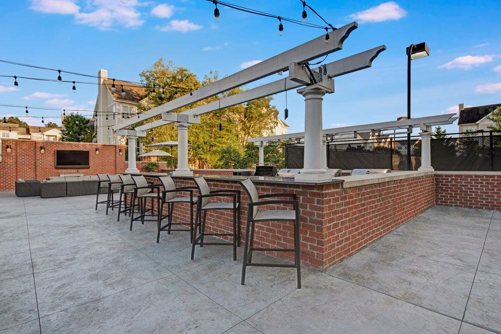 Outdoor BBQ and community seating area with bar style seating at Dulles Greene in Herndon, Virginia