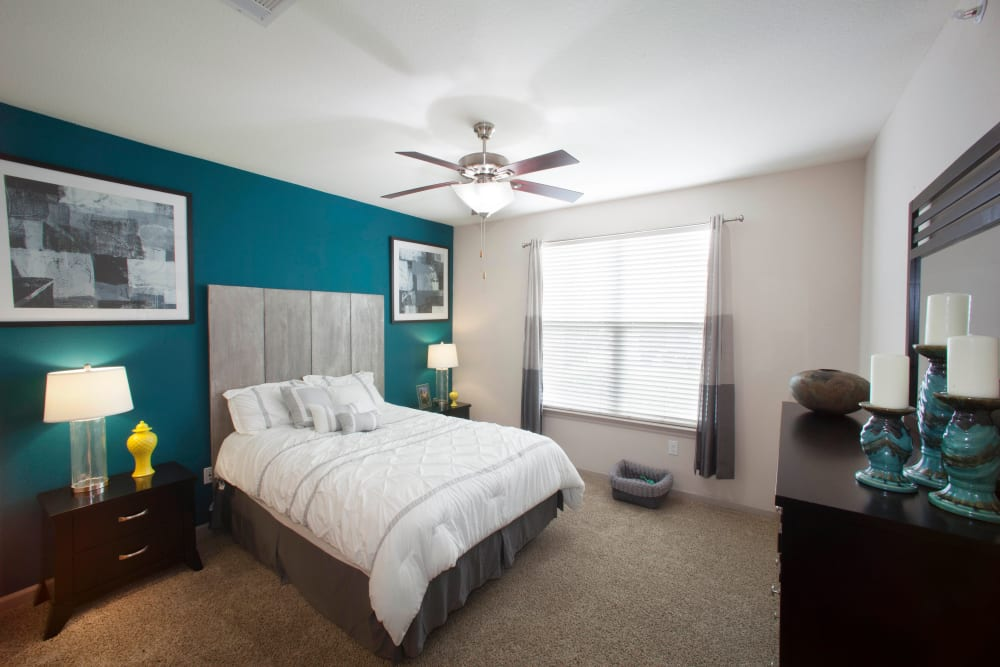 Ceiling fan and an accent wall in a model apartment's primary bedroom at Olympus Katy Ranch in Katy, Texas