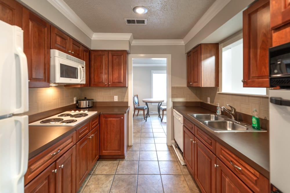 Kitchen with dark wood cabinet finishes and modern appliances at 8500 Harwood Apartment Homes in North Richland Hills, Texas