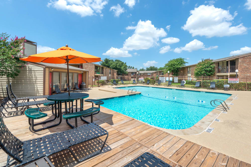 Lounge chair and table with umbrella by community pool at 8500 Harwood Apartment Homes in North Richland Hills, Texas