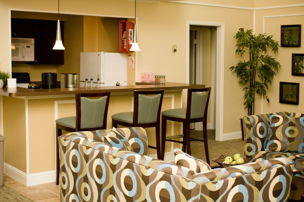 Living room and kitchen featuring breakfast bar seating at 8500 Harwood Apartment Homes in North Richland Hills, Texas