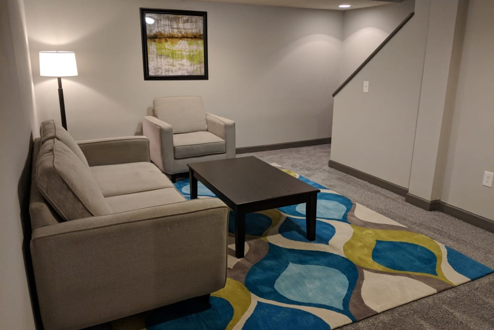 Downstairs living room with gray couches in model unit at Worthington Meadows in Columbus, Ohio