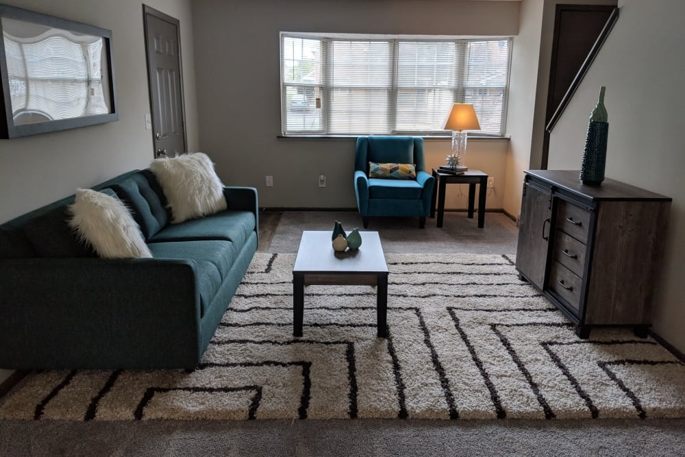 Blue couch and accent chair in downstairs common area at Worthington Meadows in Columbus, Ohio