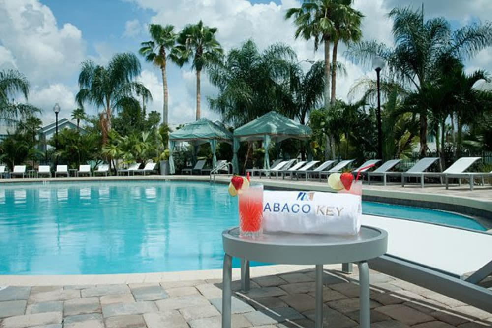 Swimming Pool with seating and drinks at Apartments in Orlando, Florida
