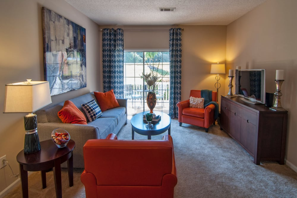 Living room space with large window and finally appointed furnishings at Amber Chase Apartment Homes in McDonough, Georgia