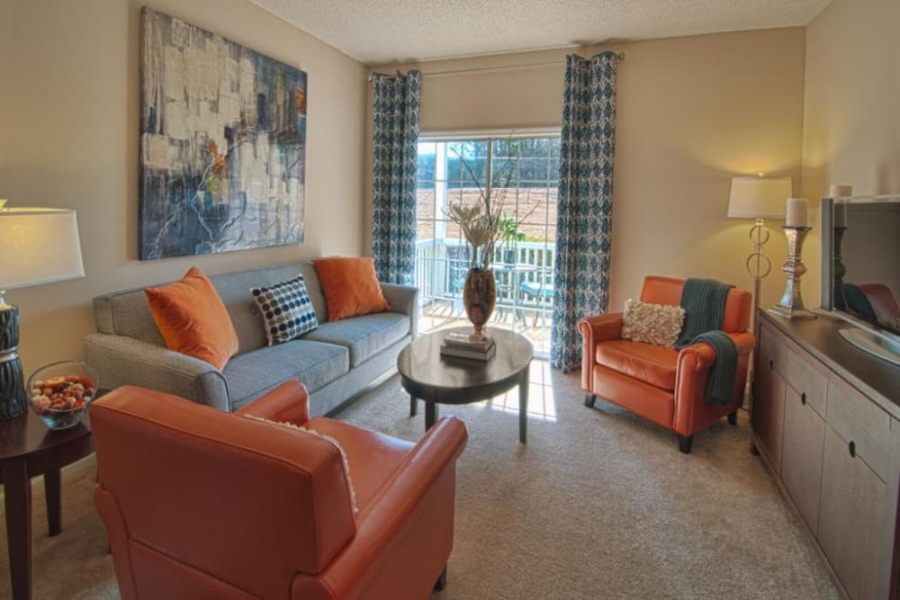 A naturally lit living room with couches and chairs at Amber Chase Apartment Homes in McDonough, Georgia