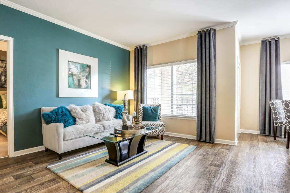 A living room complete with hardwood-style floors at Skyecrest Apartments in Lakewood, Colorado