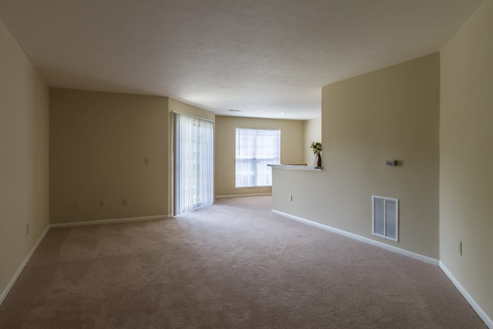 Spacious living room space with sliding glass doors that is naturally lit by a large window at Alexander Court in Reynoldsburg, Ohio