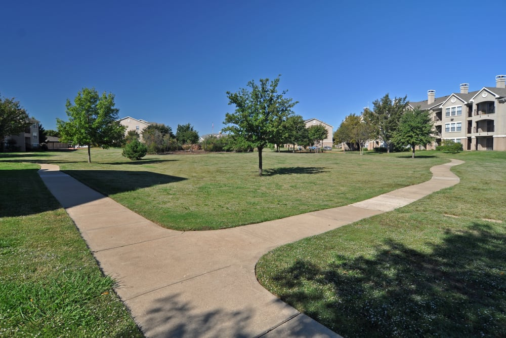 Pathways through large green field outside the apartment buildings at Arbrook Park Apartment Homes in Arlington, Texas
