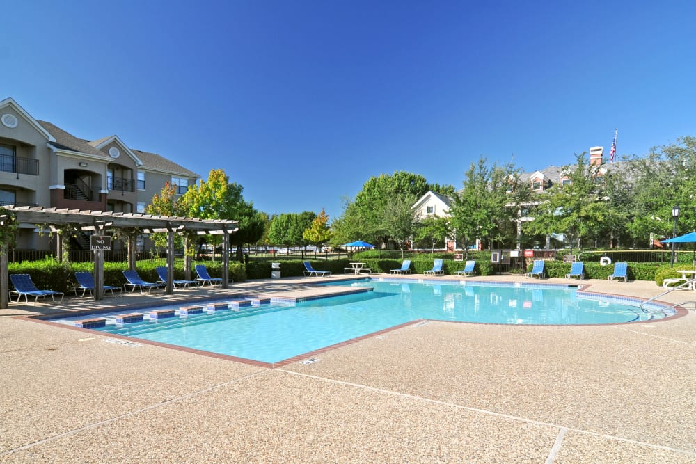 Lounge seating area and Community space by swimming pool at Arbrook Park Apartment Homes in Arlington, Texas