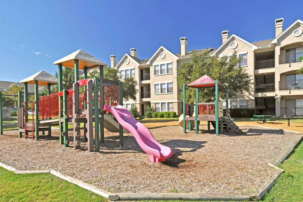 Playground equipment with brightly colored slide in apartments in the background at Arbrook Park Apartment Homes in Arlington, Texas